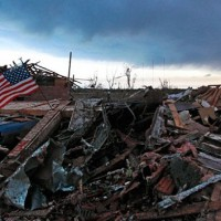 An American flag blows in the wind at sunrise atop the rubble of a destroyed home in Moore, Okla., on May 21, 2013, a day after a tornado roared through the Oklahoma City suburb, flattening entire neighborhoods and destroying an elementary school with a direct blow as children and teachers huddled against winds up to 200 mph. (Brennan Linsley/AP Photo)